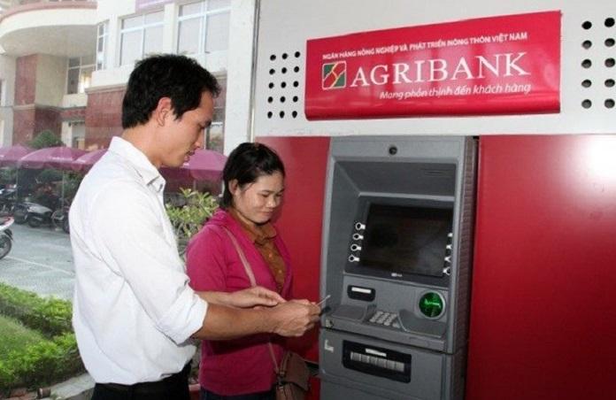 Nhân viên hỗ trợ hướng dẫn đổi mã pin mới ngay tại cây ATM trước ngân hàng.